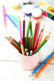 Colorful pencils in cup on the white wooden background Royalty Free Stock Image