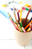 Colorful pencils in cup on the white wooden background Stock Photo