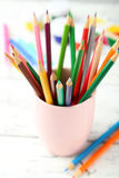 Colorful pencils in cup on the white wooden background Royalty Free Stock Photo