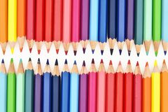 Colorful pencils facing each other on white background Royalty Free Stock Images