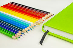 Colorful pencils and green notebook Stock Photos