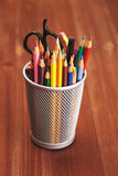 Colorful pencils in holder on wooden table Royalty Free Stock Photo