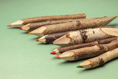 Colorful pencils made of wood, on green backdrop Royalty Free Stock Image