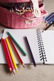 Colorful pencils and notebook on gray table Stock Images