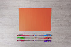 Colorful pencils and orange paper on the desk. Royalty Free Stock Photo