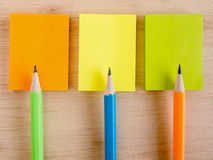 Colorful pencils put on the colorful notepads on the wooden plat Royalty Free Stock Image