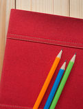 Colorful pencils put on red diary book on the wooden desk Royalty Free Stock Photos