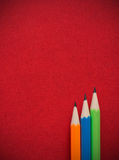 Colorful pencils put on red leather book cove Stock Images