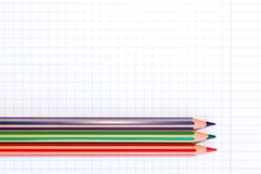 Colorful pencils of red, green and blue colors on a checkered exercise book paper with copy space stock photos