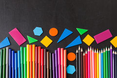 Colorful pencils in row and geometric figures on the black school chalkboard Royalty Free Stock Images