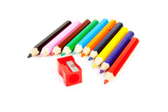 Colorful pencils in a row with sharpener Stock Photos