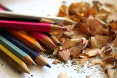Colorful pencils and shavings from sharpening pencils. Colorful shavings background. Drawing and school table background. Creativity concept Royalty Free Stock Images