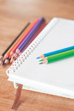 Colorful pencils on spiral notebook and green notebook Royalty Free Stock Photography