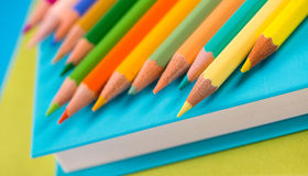 Colorful pencils on stack of books. Colorful wooden pencils on a pile of books against blue background Royalty Free Stock Photos