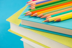 Colorful pencils on stack of books. Colorful wooden pencils on a pile of books against light blue background Royalty Free Stock Photos