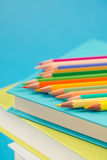 Colorful pencils on stack of books. Colorful wooden pencils on a pile of books against light blue background Stock Image