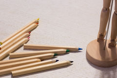 Colorful pencils on a table with puppet. Colorful pencils on a table with wood puppet Stock Photos