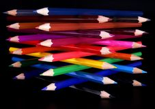 Colorful pencils tower top view. Top view of colorful pencils tower isolated over black background Royalty Free Stock Photography