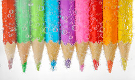Colorful pencils in water with bubbles Royalty Free Stock Photos