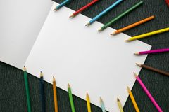 Colorful pencils on white paper copy space over wooden textured background. Backdrop for business or education design Stock Image
