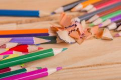 Colorful pencils. Wooden colorful pencils with sharpening shavings, on wooden table royalty free stock photo