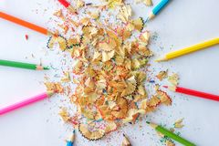 Colorful pencils and wooden shavings from pencils. On a white background Royalty Free Stock Image