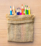 Colorful pencils in woven sack on wood Royalty Free Stock Photography