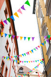 Colorful pennants hanging on house facades for street festival. Street festival with colorful pennants on ropes hanging on facades of old houses royalty free stock photography