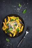 Colorful penne pasta  with parmesan cheese and basil Stock Images