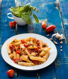 Colorful penne pasta with tomatoes Stock Images