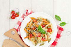 Colorful penne pasta with tomatoes and basil Stock Photography