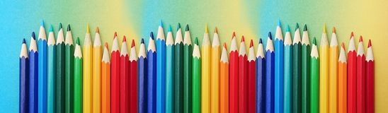 Colorful pens arranged in the colors of the rainbow on colorful paper in the course of the rainbow stock photo
