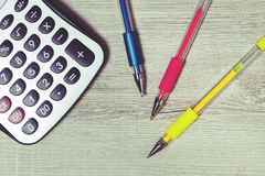 Colorful pens and calculator on the desk. Royalty Free Stock Photos
