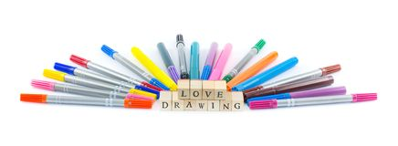Colorful pens on a white background with wooden cubes forming the sign - love drawing Stock Photos