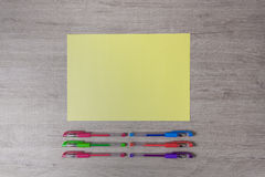 Colorful pens and yellow paper on the desk. Royalty Free Stock Images