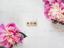 Colorful peonies and word MOM on a white background royalty free stock image