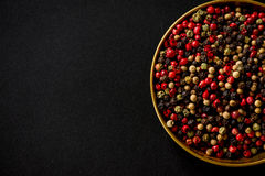 Colorful pepper seeds in golden bowl on black slate Stock Photos