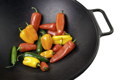 Colorful Peppers in Cast Iron Wok. Colorful sweet and jalapeno peppers in a black cast iron wok Royalty Free Stock Photos