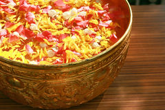 Colorful petals floating on water in golden bowl for pouring on the respected person's hand in Songkran festival stock photos