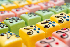 Colorful Petit fours for the party. Many colorful petit fours with marzipan and chocolate Stock Images