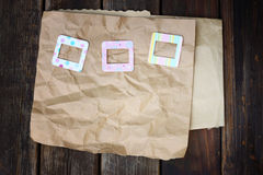 Colorful photo frames on crumpled paper on wooden background Royalty Free Stock Images