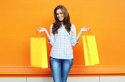 Colorful photo pretty smiling woman with two yellow shopping bag Stock Photo