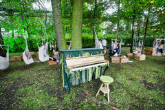 Colorful piano stands in the garden with people ride in hammocks Royalty Free Stock Photo