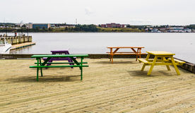 Colorful Picnic Benches on Wood Dock. Four colorful picnic benches on a dock of treated lumber at a marina Stock Photo