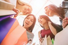 Colorful picture of girls holding colorful bags. They are looking down into one bag and wondering. Girls are looking. Very amazed and excited stock photo