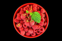 A colorful picture of raspberries on a black background. Fresh raspberries inside a bowl of red on a black background. The view from the top. Selective focus Royalty Free Stock Photography