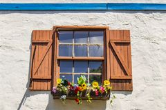 Colorful and pictureque dusty window with shutters and flowers in windowbox with shutters in white stucco wall with blue wood trim royalty free stock photography