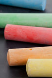 Colorful pieces of chalk on blackboard Royalty Free Stock Photos