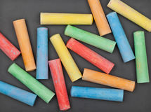 Colorful pieces of chalk on blackboard Stock Image