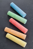 Colorful pieces of chalk on blackboard Royalty Free Stock Photography
